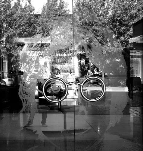 black and white photo of John Lennon on a glass door
