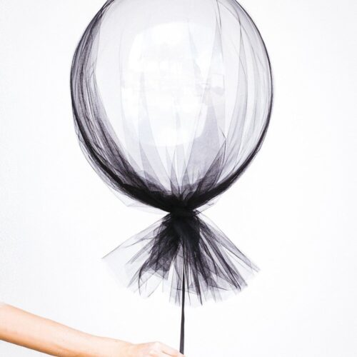 hand holding a black lace balloon