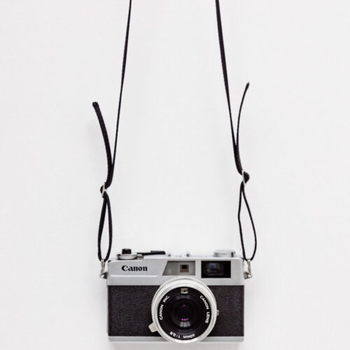 black film camera hanging on gray wall