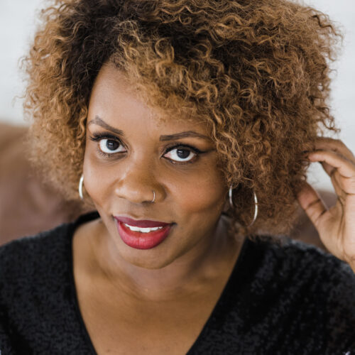 Black girl sitting on couch with blonde and brown coily hair